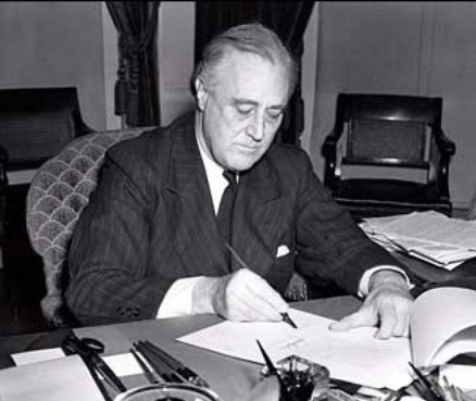 Franklin D. Roosevelt signing the Lend-Lease Act in 1941.