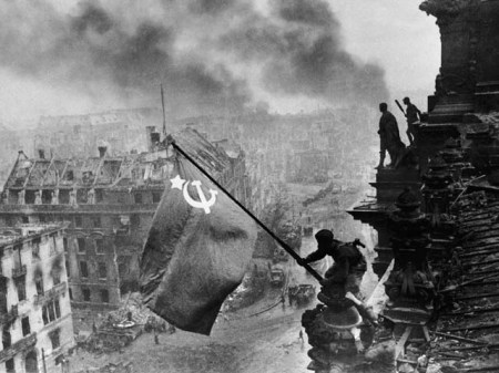 Soldiers Raise Soviet Flag Over Reichstag is a photograph by Yvgeny Khaldei.
