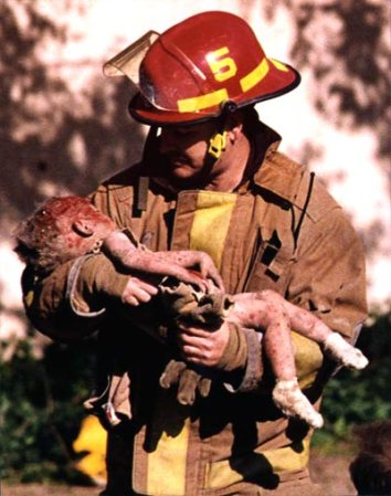 A firefighter carries an infant injured in the bombing of the Oklahoma City federal building.