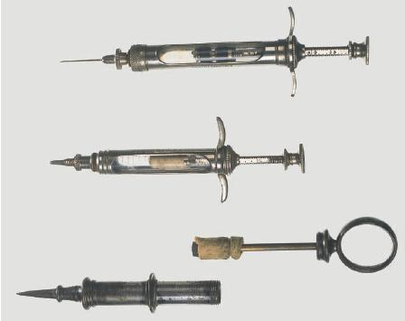 Three early syringes: at the bottom of the photo is a Pravaz syringe made of silver. The plunger (shown removed) is made of fabric and was difficult to sterilize. The top syringe dates from 1891 and has a leather plunger and a glass barrel. The middle syringe is an intermediate stage with a fabric plunger. The latter two have a screw stop mechanism on the graduated plunger stem to permit measured doses.