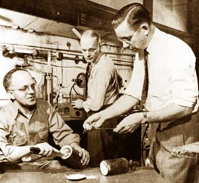 Jack Rebok, left, and Roy Plunkett, right, with another chemist, Bob McHarness, reenact the 1938 discovery of Teflon at the Jackson Laboratory, Du Pont Chambers Works, Deepwater, New Jersey.