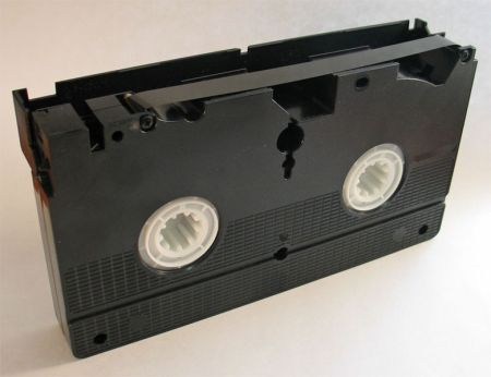 A VHS videocassette, showing the magnetic tape inside.