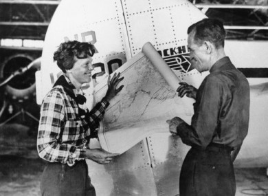 Amelia Earhard and Fred Noonan in 1937 with a map showing the route of their last flight.