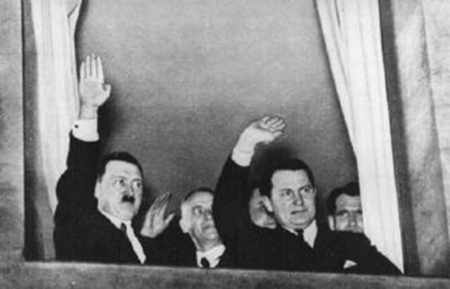Adolf Hitler and Hermann Goering wave to a torchlight parade in honor of Hitler's appointment as chancellor.