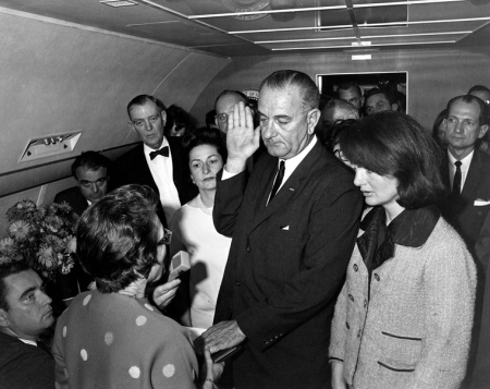 Judge Sarah T. Hughes administers the Presidential Oath of Office to Lyndon B. Johnson aboard Air Force One, at Love Field, Dallas Texas. Mrs. Johnson, Mrs. Kennedy, Jack Valenti, Cong. Albert Thomas, Cong. Jack Brooks, Associate Press Secretary Malcolm Kilduff (holding microphone) and others witness. Photograph by White House staff photographer Cecil Stoughton.