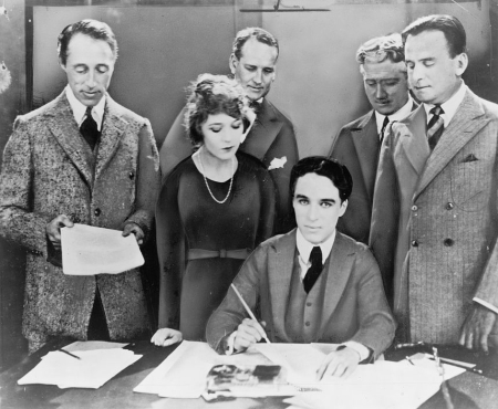 Charlie Chaplin signs the United Artists contract in 1919, with (from left) D.W. Griffith, Mary Pickford and Douglas Fairbanks standing beside him.