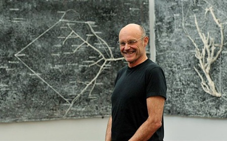 A 2011 photo of Anselm Kiefer standing in front of two of the paintings from his series 'The Secret Life of Plants for Robert Fludd' (2001-2002).