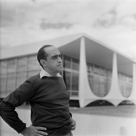 A photograph of Oscar Niemeyer in front of the Palácio da Alvorada in Brasília, by Gil Pinero.