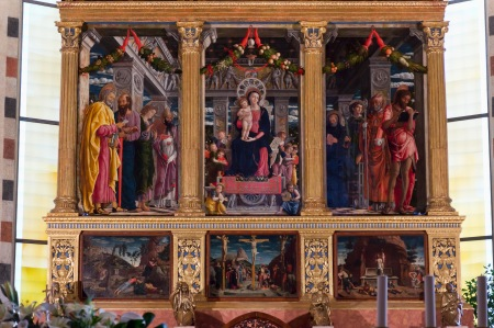 The San Zeno Altarpiece by Andrea Mantegna is missing one of the original predella paintings (The Crucifixion), which is in the Louvre in Paris.