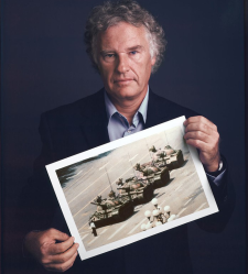 "An undated photograph of Jeff Widener with a print of ""Tank Man."""